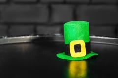 妖精的绿色帽子由毛毡制成在黑桶对一个黑暗的砖墙 圣帕特里克` s天概念 库存图片