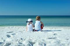 妹与兄弟坐海滩 免版税库存图片