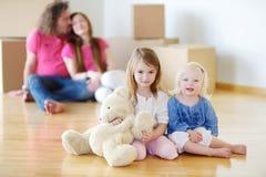 妹和他们的父母在新的家 免版税库存照片