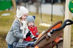 妹谈话与婴儿推车的一个婴孩 免版税库存图片