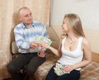 妻子产生她的丈夫货币 免版税库存图片