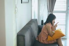 妻子和解谈的移动电话对她的丈夫在客厅,消极态度情感 库存照片