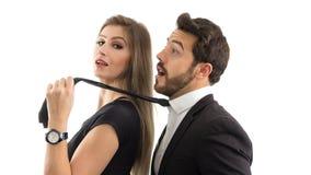 妻子由领带拉扯她的丈夫 她微笑着 服从hu 图库摄影