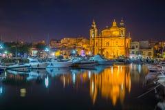 姆西达、马耳他-美丽的姆西达教区教堂有游艇和小船的和反射在水在夜之前 图库摄影