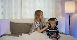 姐妹和兄弟听到与耳机的音乐在卧室 股票视频