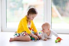 姐妹和小与玩具块的兄弟戏剧 免版税库存图片