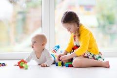 姐妹和小与玩具块的兄弟戏剧 免版税库存照片