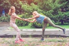 姐妹孪生一起获得乐趣在一个公园在一个夏天 库存照片