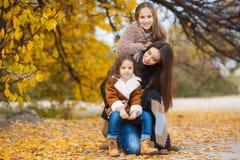 姐妹家庭画象在黄色秋天公园 图库摄影