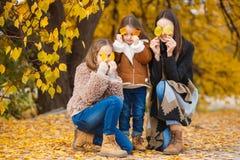 姐妹家庭画象在黄色秋天公园 免版税图库摄影