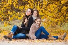 姐妹家庭画象在黄色秋天公园 免版税库存照片