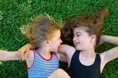 姐妹开玩笑女孩微笑的位于在庭院草 免版税图库摄影