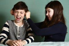 姐妹拉扯兄弟耳朵作为在论据的损失 免版税库存照片