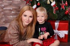 姐妹最好的朋友非常年轻一起摆在接近新年杉树和红色礼物的圣诞节演播室 逗人喜爱的adoreable g 库存照片