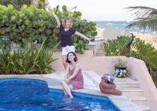 姐妹获得乐趣由水池在度假在墨西哥 免版税库存图片