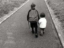 年轻姐妹走与她的更老的姐妹到学校 库存照片