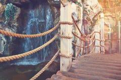 从委员会的一座桥梁和一条绳索通过瀑布在一个岩石密林 免版税库存照片