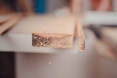 委员会的末端在锯切过程中的 工作在木材加工机器的木匠在木匠业商店 免版税库存照片
