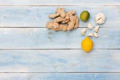 姜、大蒜和柠檬在蓝色木桌上 免版税库存图片