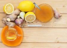 姜和蜂蜜根在木桌上 库存照片