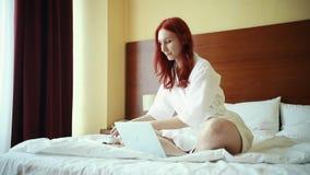 姜妇女坐床在酒店房间-饮用的茶-与膝上型计算机一起使用 股票录像