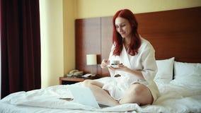 姜微笑的妇女坐在酒店房间和饮用的茶的床 股票视频