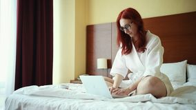 姜微笑的妇女坐床在酒店房间和与膝上型计算机一起使用 股票视频