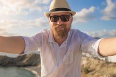 姜有胡子的男性行家旅客在与蓝色多云天空的晴朗的早晨做selfie观看背景 库存图片
