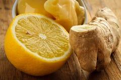 姜根、蜂蜜和柠檬在木土气桌上 免版税库存图片