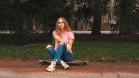 姜红头发人妇女坐longboard滑板在日出在夏天公园 股票视频
