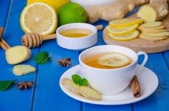 姜茶用柠檬和蜂蜜在蓝色木背景 免版税库存图片