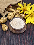 洋姜面粉在黏土碗的有花的在船上 免版税库存图片