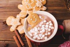 姜饼人在一个杯子沐浴巧克力或可可粉用蛋白软糖 红色杯子的姜饼人 免版税库存照片