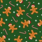 姜饼人在Xmas帽子和棒棒糖装饰在绿色背景 库存图片