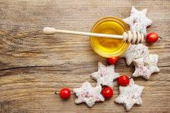 姜饼圣诞节曲奇饼和碗在木桌上的蜂蜜 库存照片