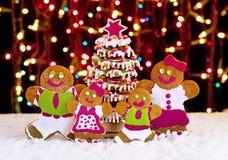姜饼在圣诞树前面的曲奇饼家庭 免版税库存照片