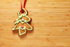 姜饼在木纹理的圣诞树曲奇饼的图象 库存照片