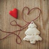姜饼垂悬在与心脏的木背景的圣诞树 图库摄影