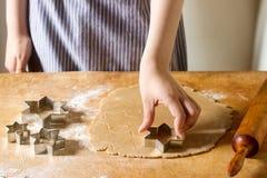 姜饼干的准备 妇女删去了曲奇饼作为星形状 烹调的酥皮点心,自创烹调概念 免版税库存照片