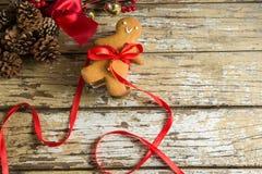 姜饼曲奇饼栓与在木板条的丝带 免版税库存图片
