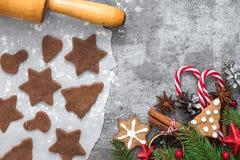 姜饼曲奇饼烹调与圣诞节和装饰的,杉树和杉木锥体在石背景 图库摄影