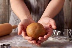 姜饼面团球在妇女手上 免版税库存图片
