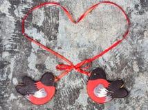 姜饼鸟红腹灰雀心脏红色丝带爱情人节概念曲奇饼形状  在灰色gr的甜曲奇饼红腹灰雀 免版税图库摄影