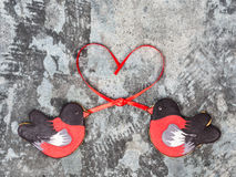 姜饼鸟红腹灰雀心脏红色丝带爱情人节概念曲奇饼形状  在灰色gr的甜曲奇饼红腹灰雀 免版税库存照片