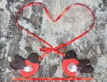 姜饼鸟红腹灰雀心脏红色丝带爱情人节概念曲奇饼形状  在灰色gr的甜曲奇饼红腹灰雀 库存图片