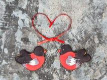 姜饼鸟红腹灰雀心脏红色丝带爱情人节概念曲奇饼形状  在灰色gr的甜曲奇饼红腹灰雀 免版税库存图片