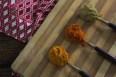 姜黄粉末,红色辣椒粉,在砧板的香菜粉末 免版税库存照片