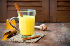 姜黄金黄牛奶拿铁用肉桂条和蜂蜜 戒毒所肝脏肥胖燃烧器,免疫促进,反激动的饮料 库存图片