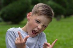 姿势的少年坐绿色草坪 免版税库存照片