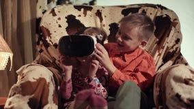 姿势示意的孩子看通过VR耳机和 股票视频